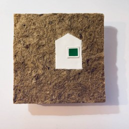 MELA M HOUSE WITH THE GREEN WINDOW SURROUNDED BY DRY GRASS